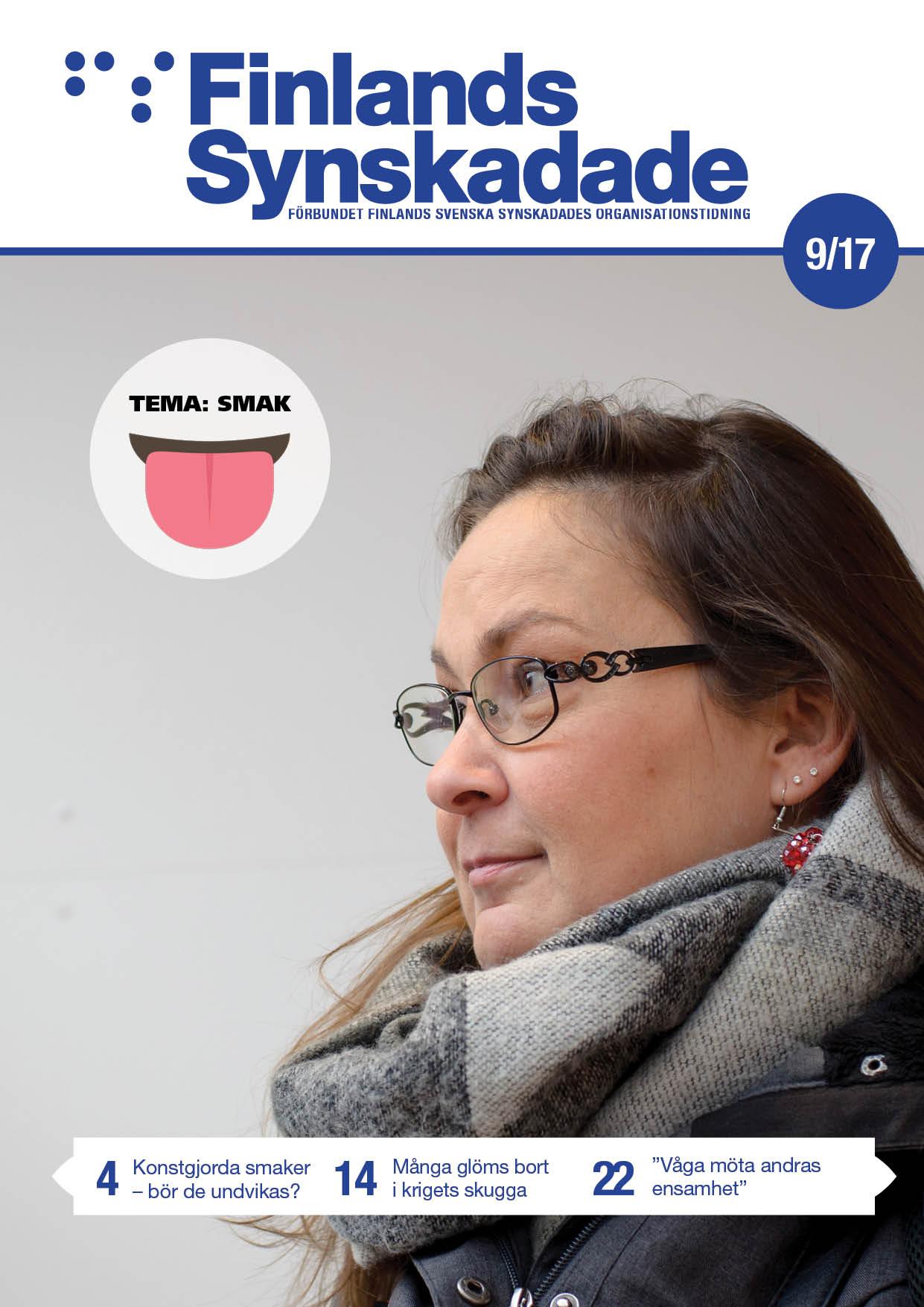 En brunhårig kvinna med stor grå skarf och glasögon tittar ut till vänster i bild.