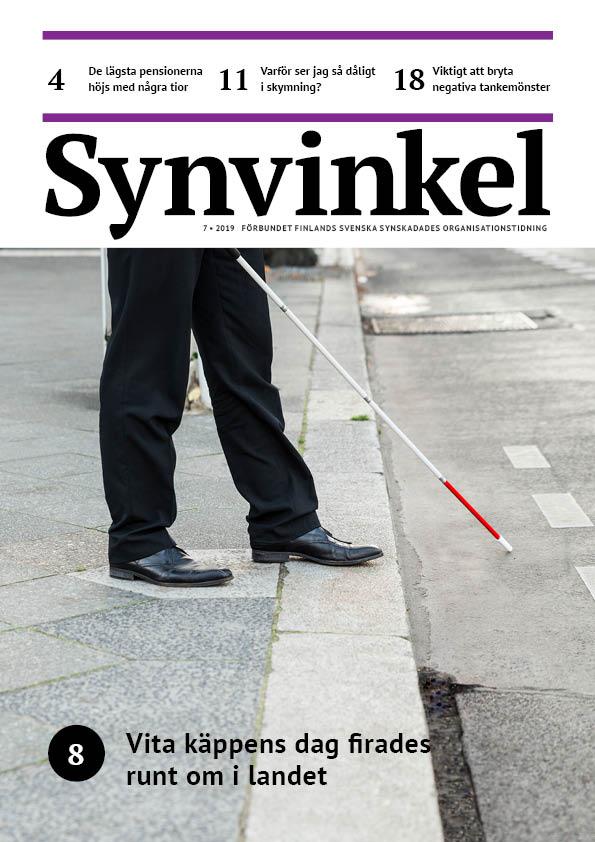 En man går med vit käpp på en gata